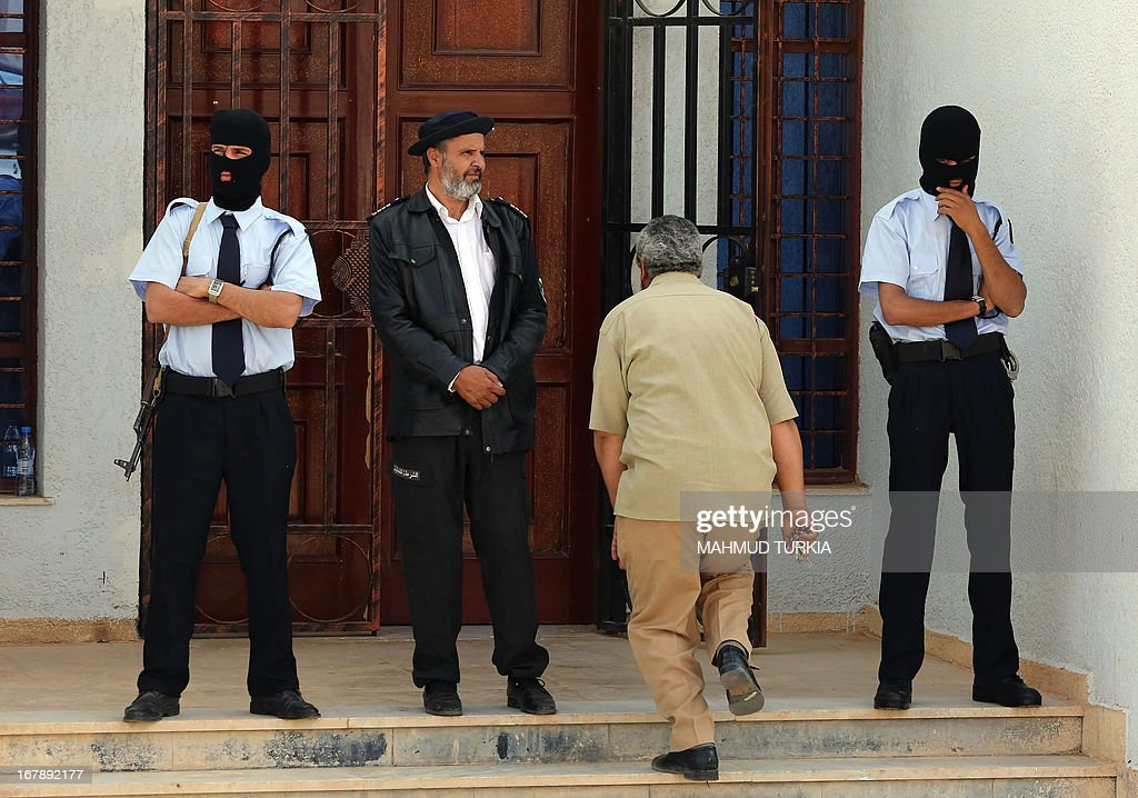 Armed and masked Libyan guards stand outside the courtroom during the trial of Seif al-Islam, son of Libya's late dictator Moamer Kadhafi, for illegally trying to communicate with the outside world in June last year, on May 2, 2013 in the northwestern town of Zintan. Two lawyers, one named by the court, represented him as he faced the charge of 'undermining state security' for meeting four envoys from the International Criminal Court.
