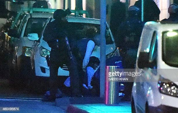 Armed Australian police engage in an operation outside a cafe in the central business district of Sydney on December 16 2014 Police stormed the...