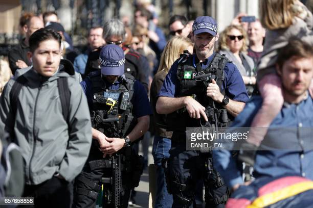 Armed British police officers carry their weapons as they patrol during an anti Brexit proEuropean Union march in London on March 25 ahead of the...