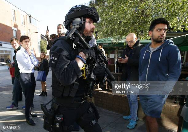 Armed British police officers stand on duty outside Parsons Green underground tube station in west London on September 15 following an incident on an...