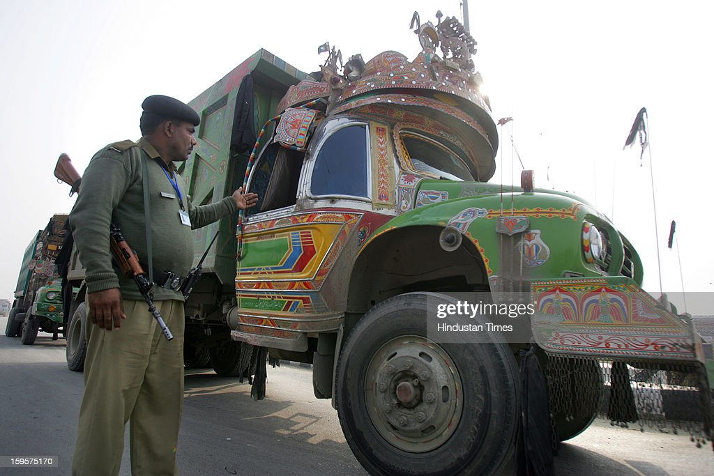 A armed BSF soldier giving signal to the a Pakistani truck driver, as he leave back for his nation after unloading the importable goods in India at Integrated Check Post (ICP) along with India-Pakistan border Attari, on January 16, 2013 near Amritsar, India. The hot words war from the both sides of the border created fear among the truck drivers whose livelihood depends upon trade between the two countries.