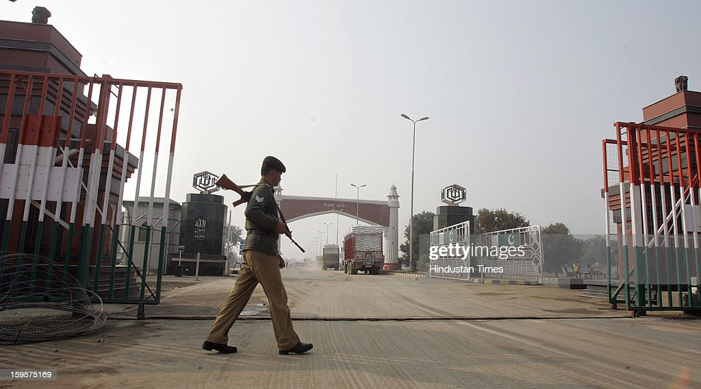 A armed BSF soldier keeping vigil on the Trade Gate with Pakistan as an Indian truck leave for Pakistan to unload the exportable goods in Pakistan at Integrated Check Post (ICP) along with India-Pakistan border Attari, on January 16, 2013 near Amritsar, India. The hot words war from the both sides of the border created fear among the truck drivers whose livelihood depends upon trade between the two countries.