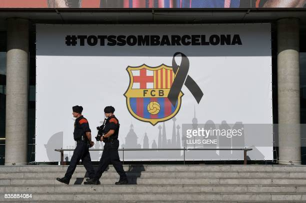 TOPSHOT Armed Catalan policemen known as Mosso d'Esquadra pass by the FC Barcelona logo with a black ribbon and a message reading 'We are all...