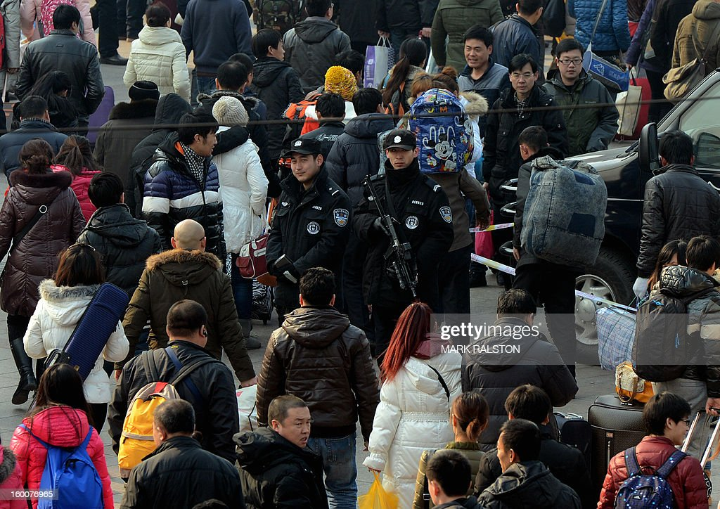 Armed Chinese police (C) stand guard as the annual Lunar New Year exodus begins at Beijing train station on January 26, 2013. The holiday also known as the Spring Festival sees tens of millions of migrant workers who provide the labour in the country's prosperous cities return to their villages and towns to spend time with the famillies left behind. AFP PHOTO/Mark RALSTON