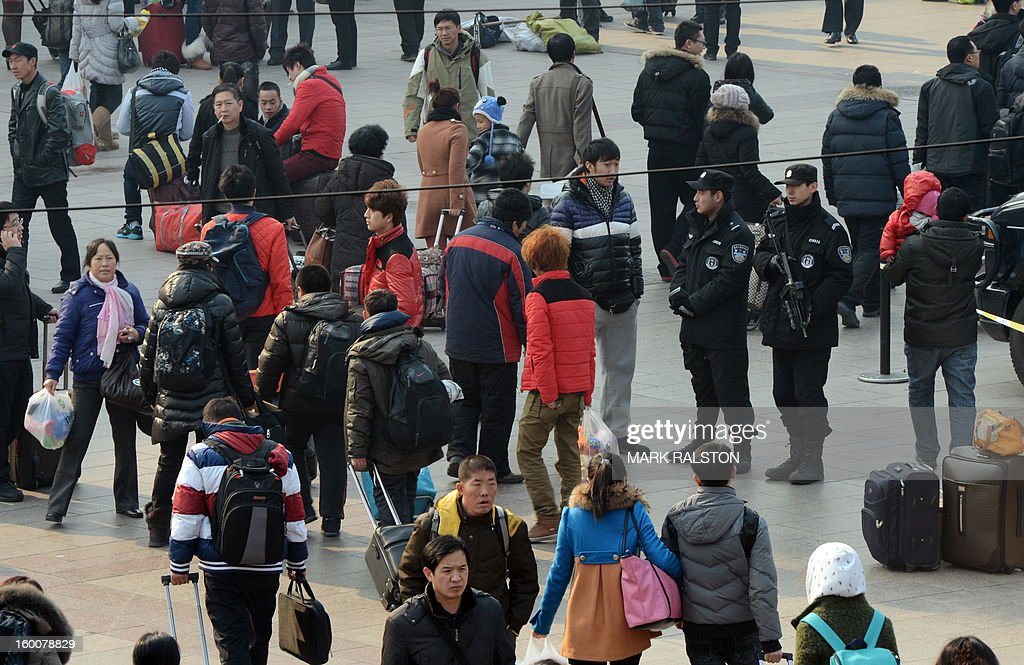 Armed Chinese police (R) stand guard as the annual Lunar New Year exodus begins at Beijing train station on January 26, 2013. The holiday also known as the Spring Festival sees tens of millions of migrant workers who provide the labour in the country's prosperous cities return to their villages and towns to spend time with the famillies left behind. AFP PHOTO/Mark RALSTON