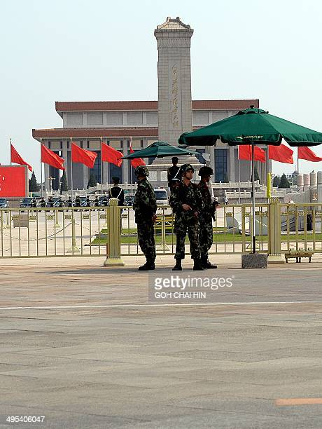 Armed Chinese police stand guard on Tiananmen Square in Beijing on June 3 2014 A steppedup police presence is visible on Beijing's streets while...