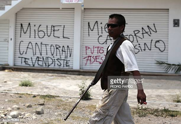 Armed civilians stand guard at the entrance to Chilapa Guerrero State Mexico on May 10 2015 About 300 people armed with rifles sticks and machetes...