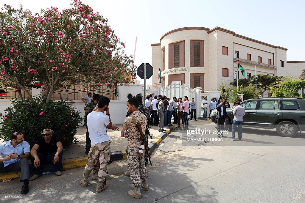 Armed demonstrators talk as their group blocks the entrance of the foreign ministry to demand it be 'cleansed of agents' and ambassadors of ousted dictator Moamer Kadhafi on April 28, 2013 in the Libyan capital Tripoli. The group prevented staff from entering the building said a ministry official who spoke to AFP. The General National Congress, Libya's highest political authority, is studying proposals for a law to exclude former Kadhafi regime officials from top government and political posts.