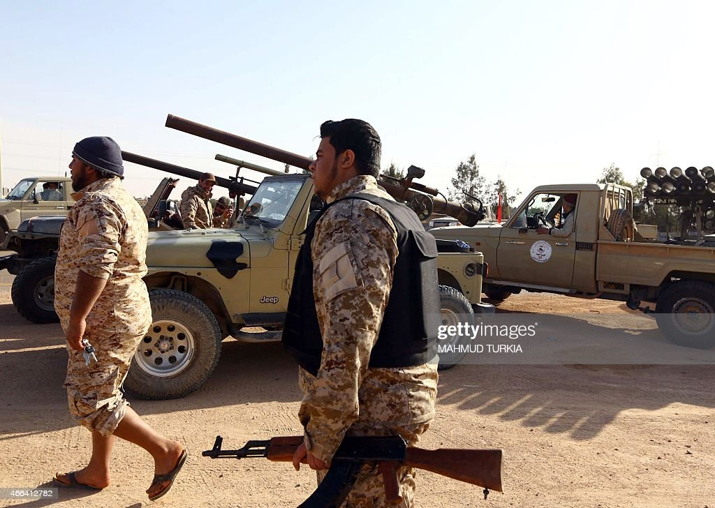 Armed fighters loyal to the Fajr Libya an alliance of Islamistbacked militias walk next to their vehicles on March 15 2015 in Libya's coastal city of...
