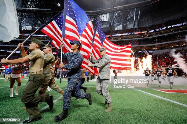Armed forces members lead the Atlanta Falcons out of the tunnel prior to the game against the Buffalo Bills at MercedesBenz Stadium on October 1 2017...