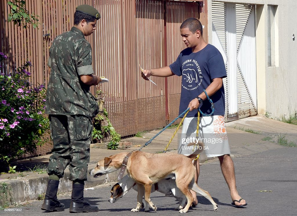 Armed forces personnel hand out flyers as part of an awareness campaign to fight the Aedes aegypti mosquito in the Metropitana neighbourhood in Brasilia, Brazil, during the day of national mobilization against the mosquito that transmits dengue and chikungunya fever and zika virus, on February 13, 2016. Some 220,000 members of the armed forces have been deployed to visit 3 million homes throughout Brazil during the day. AFP PHOTO/EVARISTO SA / AFP / EVARISTO SA