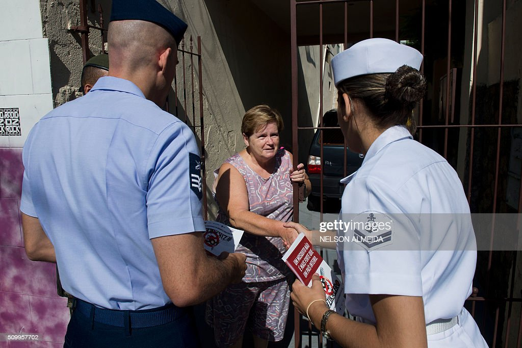 Armed forces personnel hand out flyers during an awareness campaign on the day of national mobilization against the Aedes aegypti mosquito that transmits dengue and chikungunya fever and zika virus, in Sao Paulo, Brazil on February 13, 2016. Some 220,000 members of the armed forces have been deployed to visit 3 million homes throughout Brazil during the day. AFP PHOTO / Nelson ALMEIDA / AFP / NELSON ALMEIDA