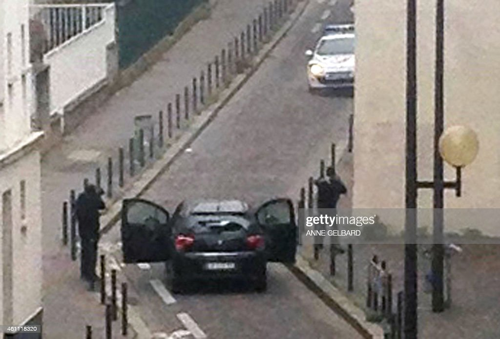 Armed gunmen face police officers near the offices of the French satirical newspaper Charlie Hebdo in Paris on January 7 during an attack on the...