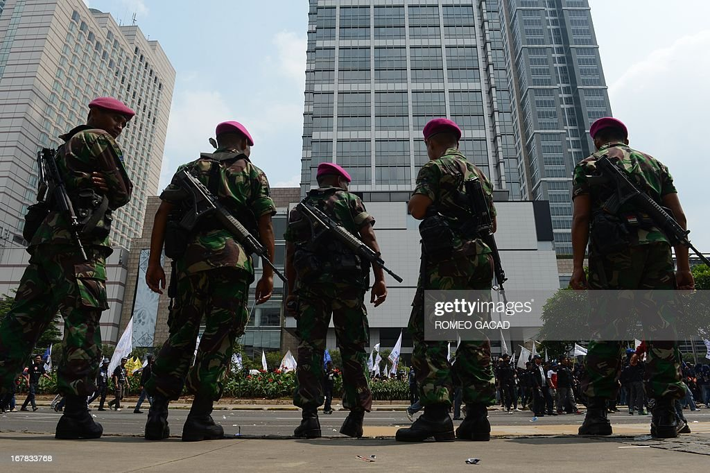 Armed Indonesian soldiers stand along the roadside while thousands of workers march to the presidential palace in Jakarta on May 1, 2013 to mark Labour Day in protest against outsourcing policy and low wages. According to the police about 55,000 workers participated in the Labour Day rally while thousands of police and troops were mobilized for security.