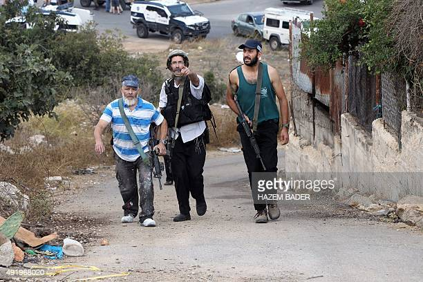 Armed Israeli settlers walk up a road at the site of a reported stabbing attack by a Palestinian on an Israeli settler near the Israeli settlement of...