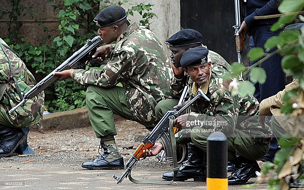Armed Kenyan policemen take cover outside the Westgate mall in Nairobi on September 23 2013 Kenyan troops were locked in a fierce firefight with...