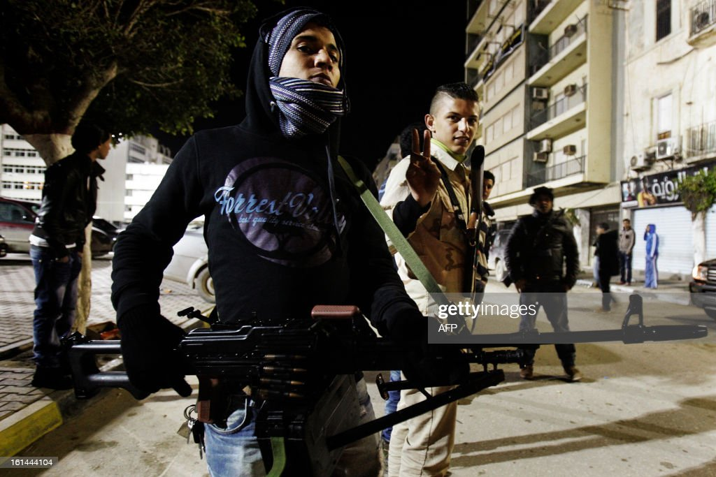 Armed Libyan civilians man a checkpoint in one of the streets of Benghazi on February 11, 2013, as Libyans formed small armed to protect their neighborhood from possible threats as the 2nd anniversary of the libyan revolution is few days away. AFP PHOTO/ABDULLAH DOMA