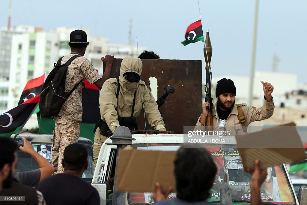 Armed Libyan men wave their national flags during a demonstration marking the fifth anniversary of the Libyan revolution which toppled strongman...