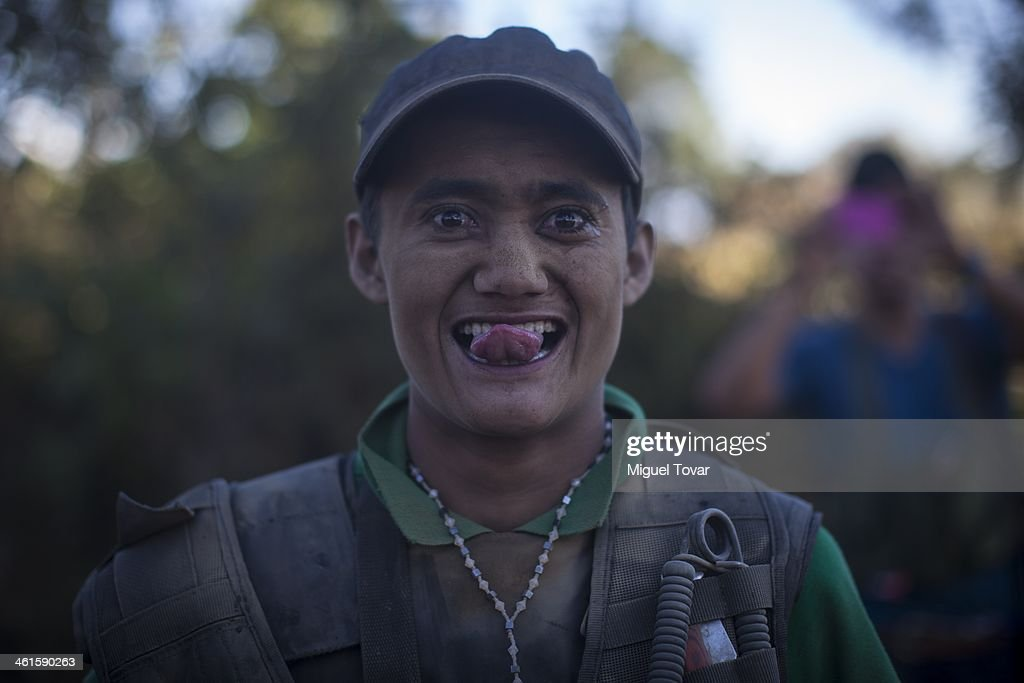 Armed man of the self-defense group jokes during a patrol at the mountain range in the outskirt of Paracuaro, in the state of Michoacan, Mexico. Despite some success by self-defense groups to free a few municipalities from the Knights Templar cartel, the cartel continues to enforce a stranglehold on other parts of Michoacan, a rich farming state that is a major exporter of lime, avocado and mango on January 08, 2014 in Mexico Paracuaro, Mexico.