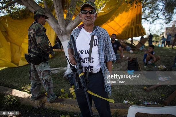 Armed man of the selfdefense group stands guard in a checkpoint at Paracuaro in the state of Michoacan Mexico Despite some success by selfdefense...