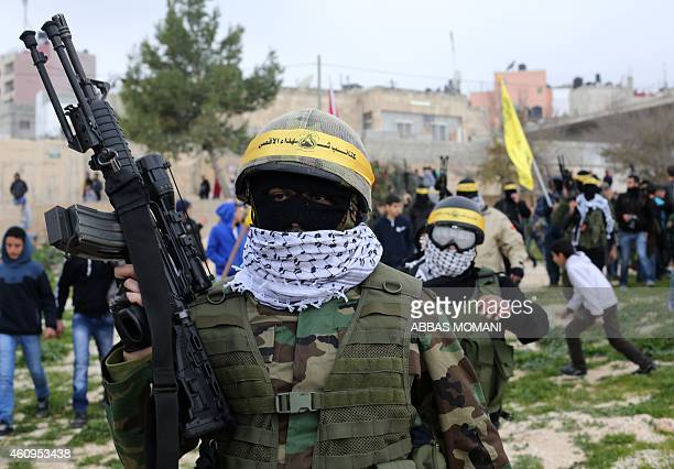 Armed members of the alAqsa Martyrs Brigades the Palestinian Fatah movement's armed wing take part in a march to mark the 50th anniversary of the...