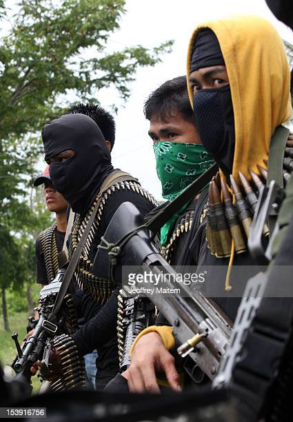 Armed members of the breakaway faction of the Moro Islamic Liberation Front walk congregate in a village ahead of the signing of an agreement between...