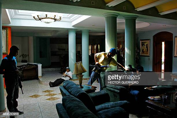 Armed members of the SelfProtection militia stand guard inside the house of drug trafficker aka 'El botas' in Paracuaro state of Michoacan Mexico on...