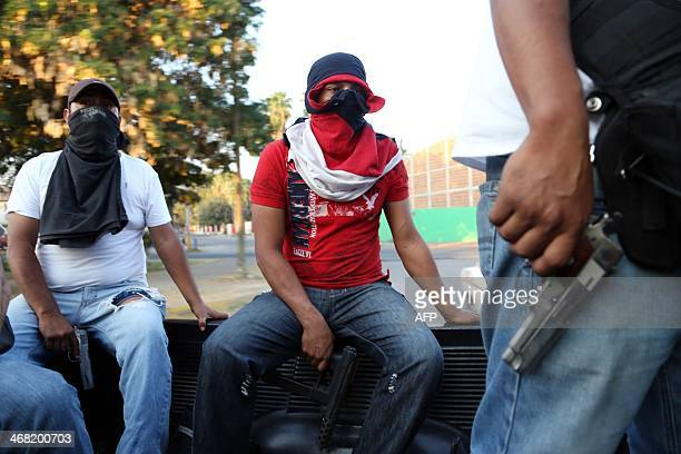 Armed members of the socalled selfdefence groups patrol streets of Apatzingan in the state of Michoacan Mexico on February 9 2014 Vigilante militias...