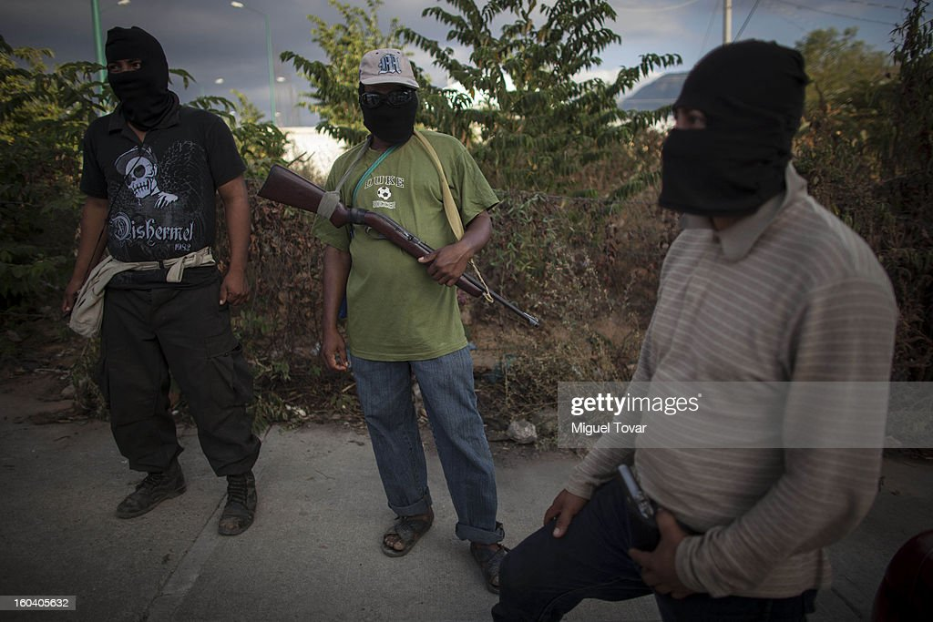 Armed men guard a roadblock at the entrance to the community of Ayutla on January 29, 2013 in Ayutla, Mexico. Hundreds of men have taken up arms in several towns of the southern state of Guerrero to defend their communities against violent criminal gangs.