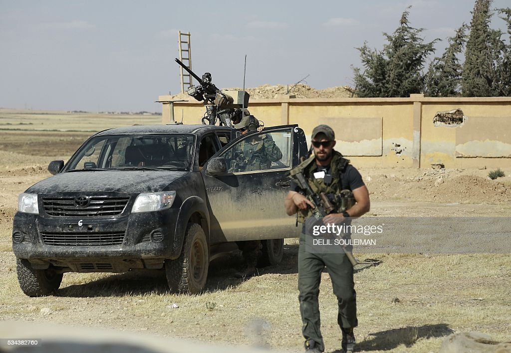 Armed men identified by Syrian Democratic forces as US special operations forces are seen in the village of Fatisah in the northern Syrian province of Raqa on May 25, 2016. US-backed Syrian fighters and Iraqi forces pressed twin assaults against the Islamic State group, in two of the most important ground offensives yet against the jihadists. The Syrian Democratic Forces (SDF), formed in October 2015, announced on May 24 its push for IS territory north of Raqa city, which is around 90 kilometres (55 miles) south of the Syrian-Turkish border and home to an estimated 300,000 people. The SDF is dominated by the Kurdish People's Protection Units (YPG) -- largely considered the most effective independent anti-IS force on the ground in Syria -- but it also includes Arab Muslim and Christian fighters. SOULEIMAN