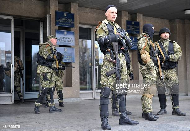 Armed men in military fatigues stand guard outside a regional administration building they seized in the eastern Ukrainian city of Slavyansk on April...