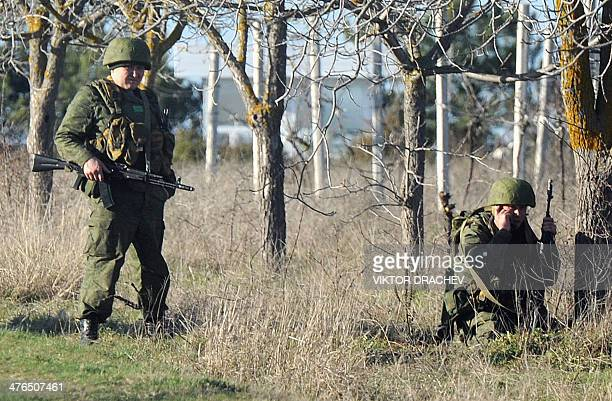 Armed men in uniform stand guard as they block the Ukrainian military airforce aerodrome in Belbek near Sevastopol on March 3 2014 Russian forces...