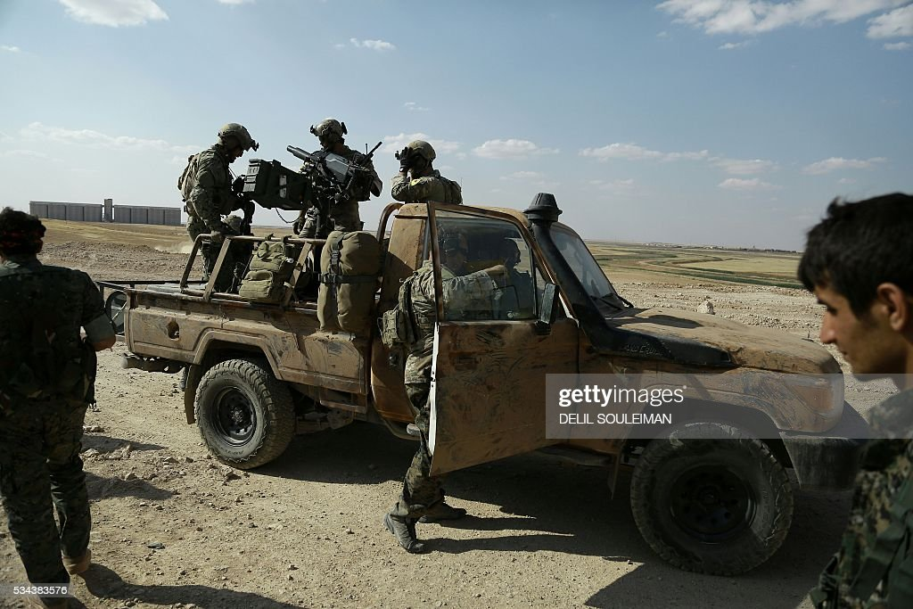 Armed men in uniforms identified by Syrian Democratic forces as US special operations forces stand in the back of a pickup truck in the village of Fatisah in the northern Syrian province of Raqa on May 25, 2016. US-backed Syrian fighters and Iraqi forces pressed twin assaults against the Islamic State group, in two of the most important ground offensives yet against the jihadists. The Syrian Democratic Forces (SDF), formed in October 2015, announced on May 24 its push for IS territory north of Raqa city, which is around 90 kilometres (55 miles) south of the Syrian-Turkish border and home to an estimated 300,000 people. The SDF is dominated by the Kurdish People's Protection Units (YPG) -- largely considered the most effective independent anti-IS force on the ground in Syria -- but it also includes Arab Muslim and Christian fighters. SOULEIMAN