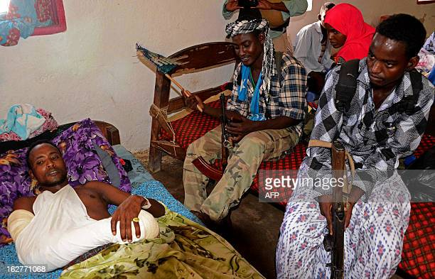 Armed men keep watch over an injured man at a clinic in Kismayo Somalia on February 26 2013 Recent clashes broke out between rival progovernment...