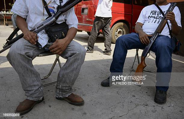 Armed men members of a vigilante group keep watch in Coalcoman community in Michoacan State Mexico on May 22 2013 Vigilante groups calling themselves...