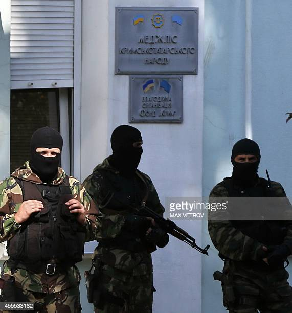 Armed men stand guard in front of the entrance of the Mejlis of the Crimean Tatar people in Simferopol on September 16 2014 Russian police on...