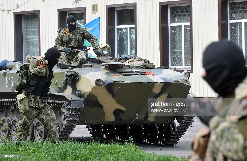 Armed men wearing military fatigues gather around Armoured Personnel Carriers seized to the Ukrainian army as they stand guard outside the regional...