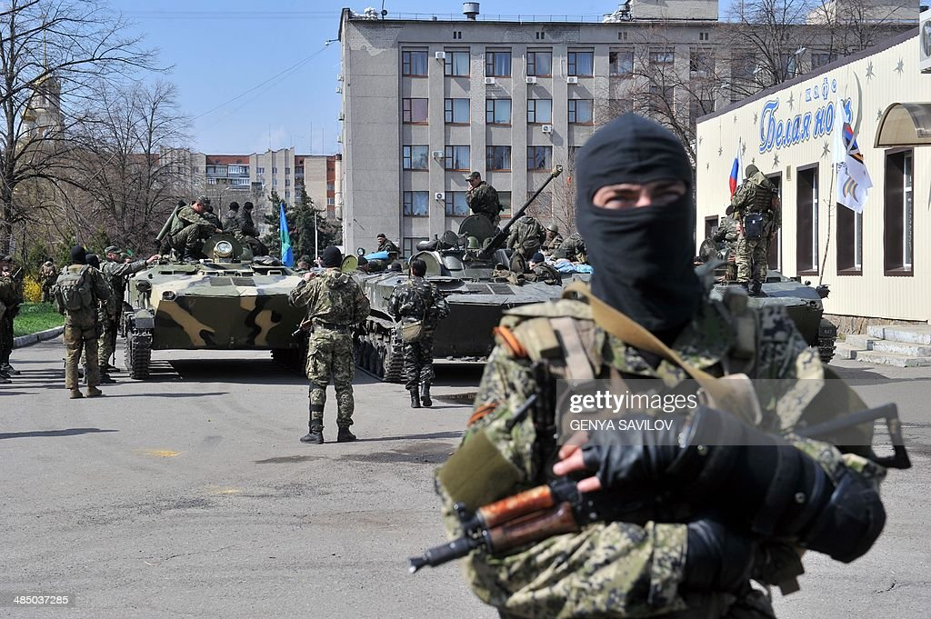Armed men wearing military fatigues gather by Armoured Personnel Carriers (APC) seized to the Ukrainian army as they stand guard outside the regional state building seized by pro-Russian separatists in the eastern Ukrainian city of Slavyansk on April 16, 2014. Ukraine's Western-backed prime minister on April 16 accused Russia of erecting a new 'Berlin Wall' that threatened European security. 'Today's events... are starting to endanger Europe and the European Union. It is now clear that our Russian neighbours have decided to build a new Berlin Wall and return to the Cold War era,' Arseniy Yatsenyuk told a government meeting. AFP PHOTO /GENYA SAVILOV