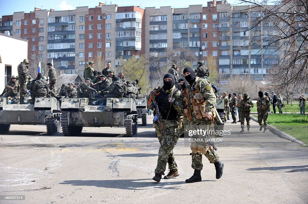 Armed men wearing military fatigues gather by Armoured Personnel Carriers seized to the Ukrainian army as they stand guard outside the regional state...