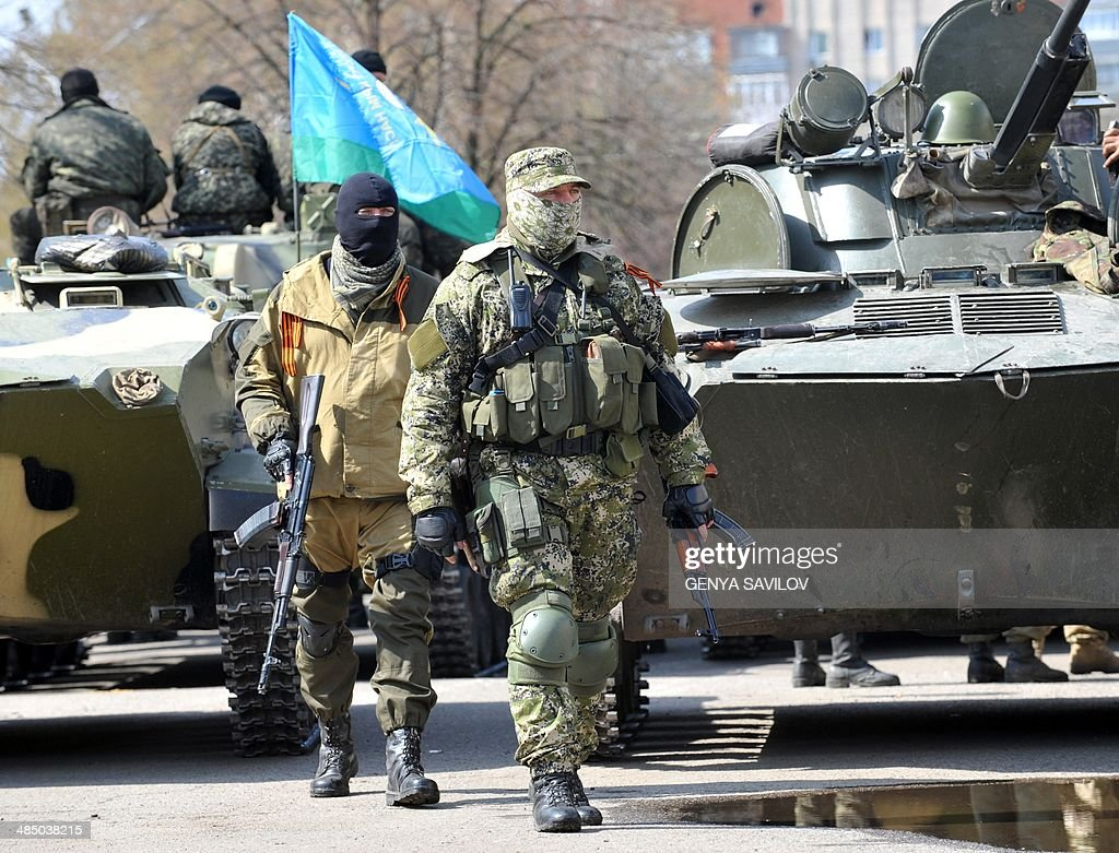 Armed men wearing military fatigues gather by Armoured Personnel Carriers (APC) seized to the Ukrainian army as they stand guard outside the regional state building seized by pro-Russian separatists in the eastern Ukrainian city of Slavyansk on April 16, 2014. Russian leader Vladimir Putin warned that Ukraine is on the verge of civil war, the Kremlin said Wednesday, after the Kiev government sent in troops against pro-Moscow separatists in the east of the country.