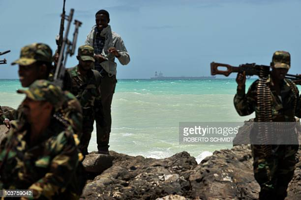 Armed militiamen and a pirate walk on a rocky outcrop on the coast in the central Somali town of Hobyo as a a hijacked Korean supertanker lies...