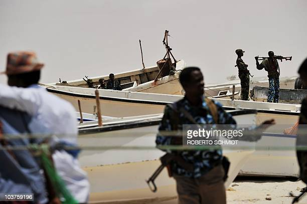 Armed militiamen and some pirates stand among fishing boats on the coast in the central Somali town of Hobyo on August 20 2010 The fledging Galmadug...