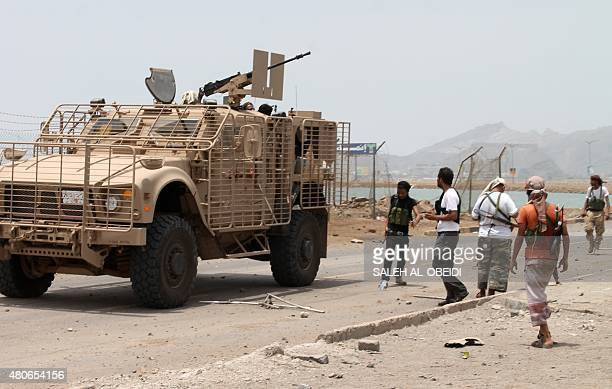 Armed militiamen loyal to Yemen's fugitive President Abderabbo Mansour Hadi stand next to an armed vehicle in the Khor Maskar neighbourhood of the...