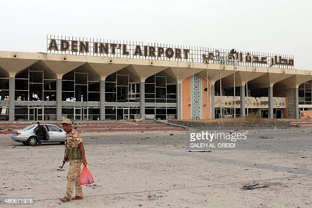 Armed militiamen loyal to Yemen's fugitive President Abderabbo Mansour Hadi stand at the entrance to Aden's international airport on July 14 2015...