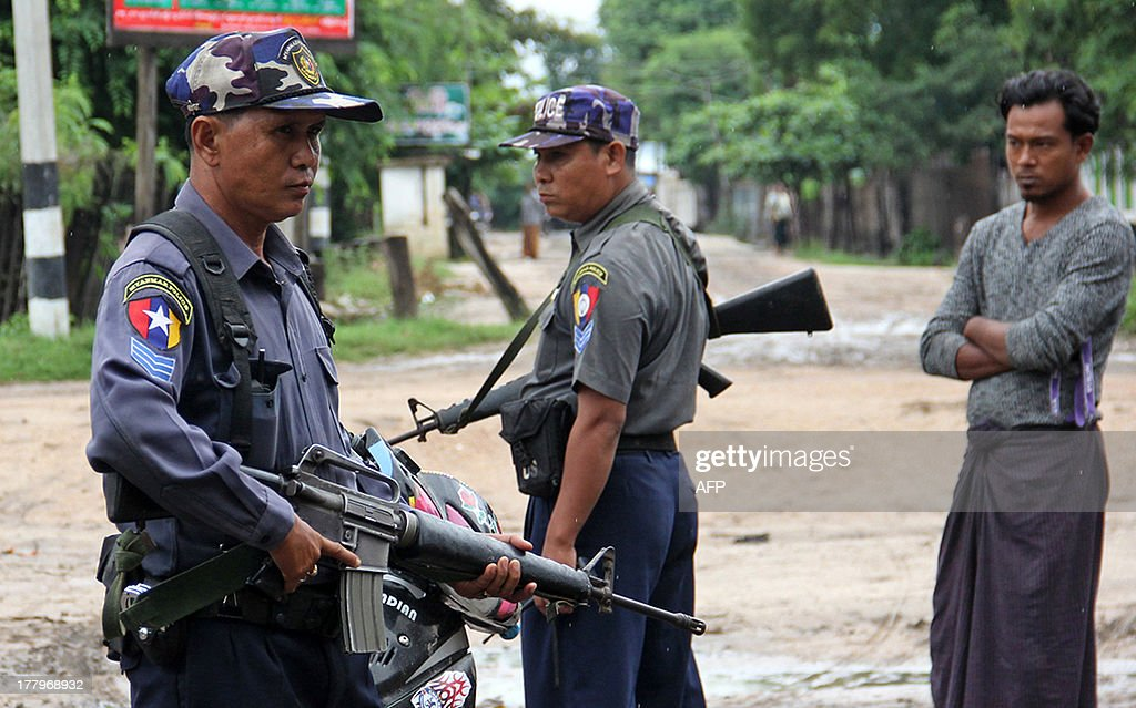 Armed Myanmar policemen stand on alert in the streets of Htan Gone village on August 26, 2013 after some 1,000 anti-Muslim rioters rampaged through villages in Kanbalu township, in the central region of Sagaing, setting fire to property and attacking rescue vehicles on August 24. Hundreds of people made homeless by Myanmar's latest eruption of religious violence were sheltering in a school on August 26, a local MP said, after mobs torched the homes and shops of local Muslims.