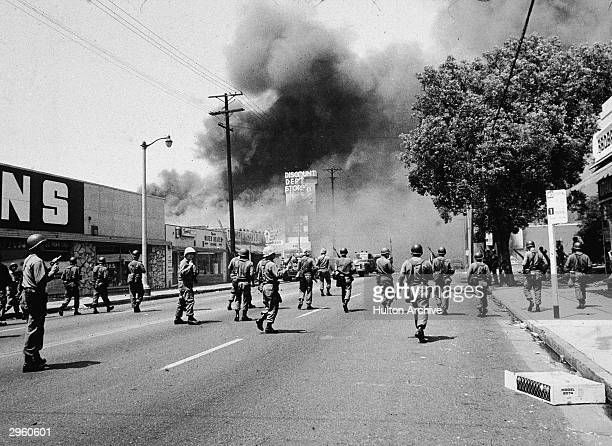 Armed National Guardsmen march toward smoke on the horizon during the street fires of the Watts riots Los Angeles California August 1965