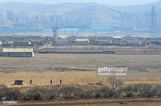 Armed North Korean soldiers on border patrol walk across farmland some 30 km northeast of the border town of Sinuiju on April 6 which is across the...