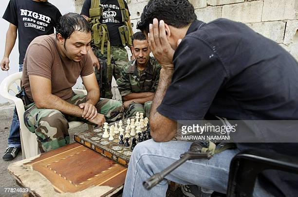 Armed Palestinian men use chess blocks to play 'dama' in an alley in the refugee camp of Ain elHelweh in the outskirts of the southern Lebanese port...