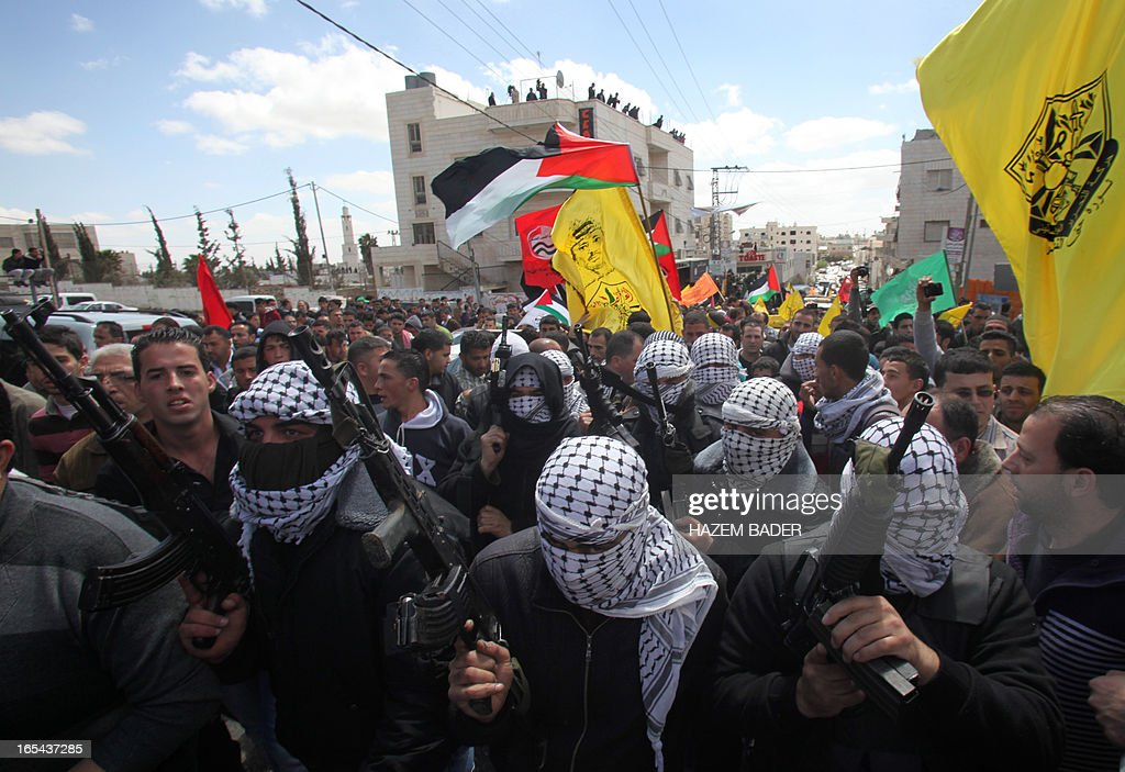 Armed Palestinian militants attend the funeral of Maisara Abu Hamdiya, a Palestinian prisoner who died of cancer while in Israeli detention, in the West Bank city of Hebron April 4, 2013. The West Bank simmered with anger as thousands joined the funeral of a prisoner who died in an Israeli jail and similar numbers gathered to bury two teens shot dead overnight. AFP PHOTO/HAZEM BADER