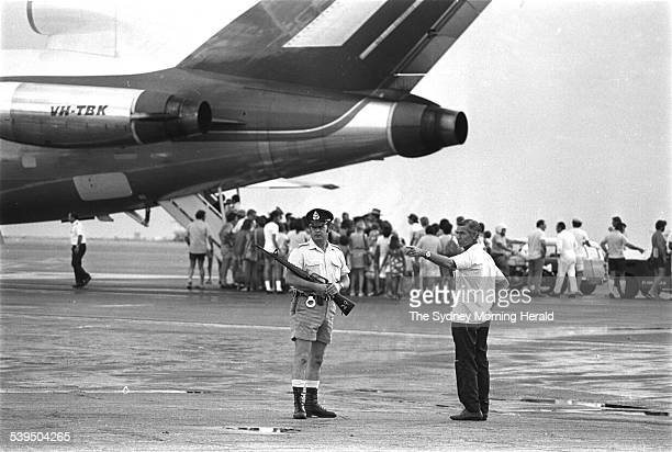 Armed police at Darwin Airport watch evacuees board for Sydney Melbourne Brisbane after Cyclone Tracy 26 December 1974 SMH Picture by RICK STEVENS
